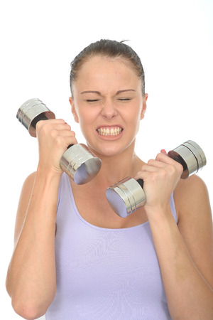 clenching teeth: Healthy Young Woman Clenching Her Teeth Training With Weights Looking Strained or Stressed