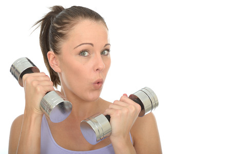 dumb: Healthy Young Woman Training With Dumb Bell Weights Looking Shocked or Surprised Stock Photo