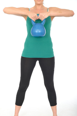 kettle bell: Attractive Healthy Young Woman Working Out Lifting a 5kg Kettle Bell Weight