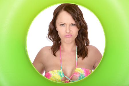 miserable: Attractive Miserable Frowning Young Woman Looking Through a Green Rubber Ring