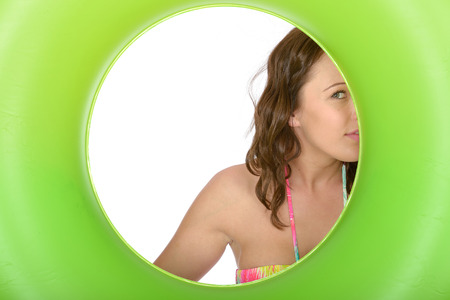 coy: Attractive Cheeky Playful Coy Young Woman Looking Through a Green Rubber Ring Stock Photo