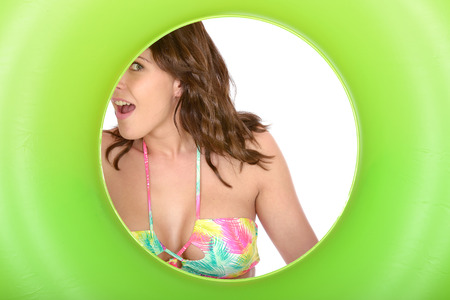 rubber ring: Attractive Cheeky Playful Coy Young Woman Looking Through a Green Rubber Ring Stock Photo