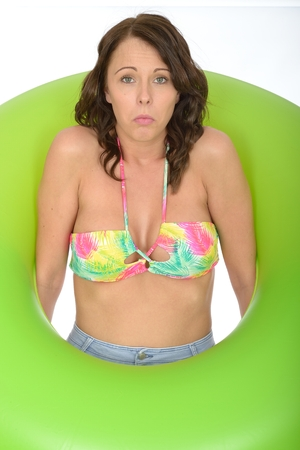 rubber ring: Attractive Unhappy Young Woman Looking Through a Green Rubber Ring Stock Photo