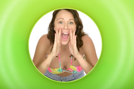 rubber ring: Attractive Young Woman Looking Through a Green Rubber Ring Shouting