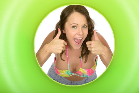 rubber ring: Attractive Young Woman Looking Through a Green Rubber Ring Giving Thumbs Up Sign