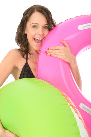 inflated: Happy Young woman On Holiday Holding Inflated Rubber Rings Laughing and Smiling
