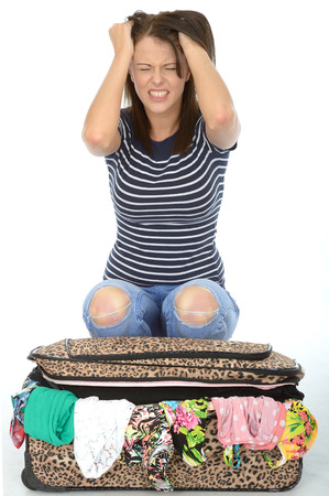 overflowing: Unhappy Frustrated Upset Attractive Young Woman Sitting on an Overflowing Suitcase Stock Photo