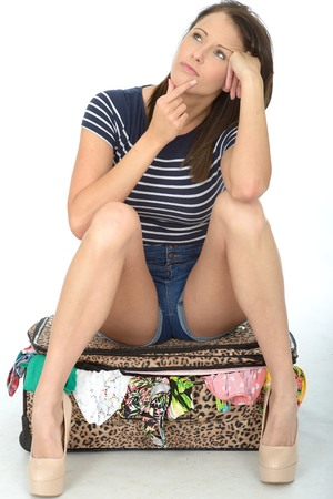 fed up: Sad Unhappy Worried and Fed Up Young Woman Wearing Shorts Sitting on an Overflowing Suitcase