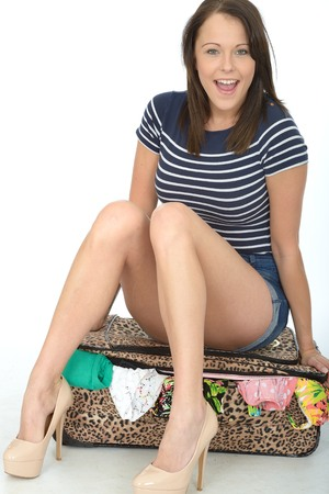 a situation alone: Attractive Happy Young woman Sitting on a Packed Overflowing Suitcase Smiling and Looking Happy Wearing Blue Shorts