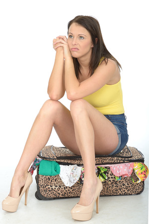 a situation alone: Miserable Sexy Bored Young Woman Sitting on a Suitcase in Blue Shorts and a Yellow Vest Top in High Heel Shoes