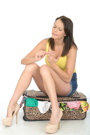 fingers on top: Attractive Confused and Concerned Young Woman Sitting on a Suitcase Counting on Her Fingers Wearing a Yellow Vest Top and High Heels