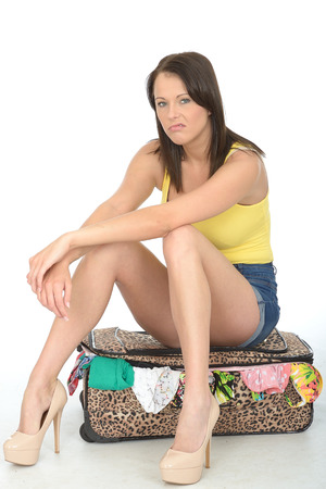 miserable: Sexy Miserable Fed Up Young Woman Sitting on a Suitcase Resting on Her Knees Looking Unhappy Stock Photo