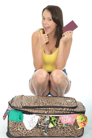 Pleased Young Woman Kneeling Behind a Suitcase Holding a Passport Smiling and Looking Happy photo