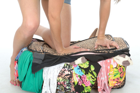 a situation alone: Close Up of Young Woman Kneeling on Suitcase Trying to Close it With Clothes Spilling Out Stock Photo