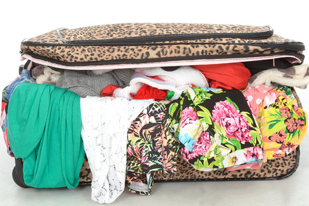 Overflowing Full Suitcase Unable to Close With Clothes Spilling Out Unzipped Stock Photo
