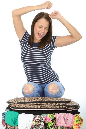 mujer arrodillada: Feliz Mujer joven atractiva que se arrodilla en una maleta que desborda Celebrando con los ojos cerrados