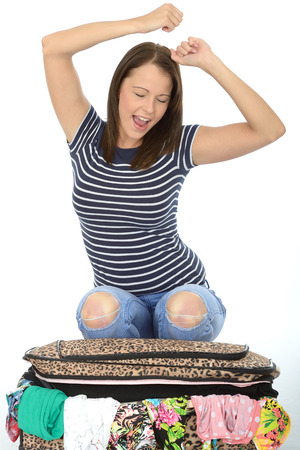 Happy Attractive Young Woman Kneeling on an Overflowing Suitcase Celebrating With Her Eyes Closed Stock Photo