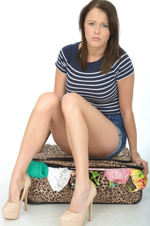 Sad Unhappy Worried and Fed Up Young Woman Wearing Shorts Sitting on an Overflowing Suitcase
