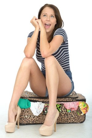 overflowing: Attractive Happy Young woman Sitting on a Packed Overflowing Suitcase Smiling and Looking Happy Wearing Blue Shorts