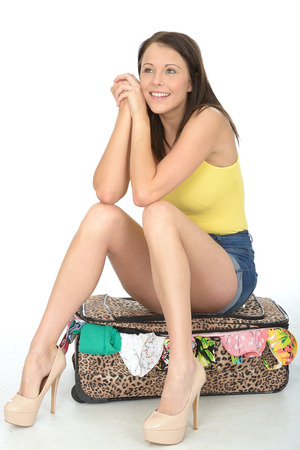 vest top: Sexy Happy Smiling Young Woman Sitting on a Packed Suitcase Looking Happy Wearing a Yellow Vest Top and High Heel Shoes