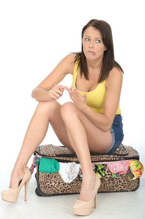 vest top: Attractive Confused and Concerned Young Woman Sitting on a Suitcase Counting on Her Fingers Wearing a Yellow Vest Top and High Heels