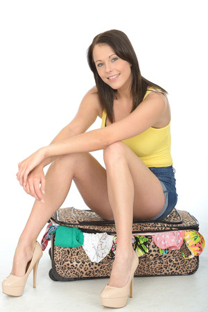 vest top: Happy Relaxed Young Woman Sitting on a Suitcase Looking Happy and Smiling Wearing a Yellow Vest Top and High Heel Shoes