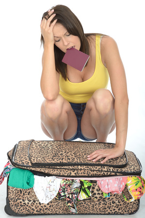fed up: Fed UP and Frustrated Young Woman Trying to Close Her Suitcase With a Passport in Her Mouth Wearing a Yellow Vest Top