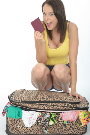 Pleased Young Woman Kneeling Behind a Suitcase Holding a Passport Smiling and Looking Happy