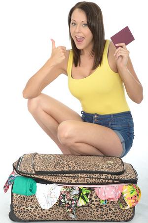 mujer rodillas: Satisfecho Joven mujer de rodillas detrás de una maleta con pasaporte Sonriente y buscando feliz Foto de archivo