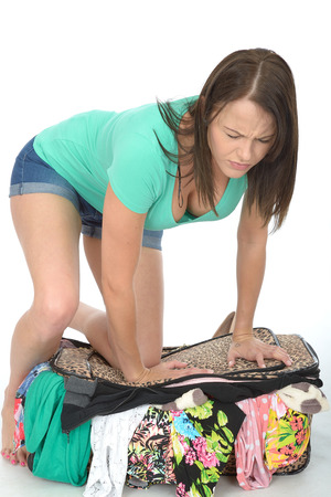 a situation alone: Frustrated Attractive Young Woman Trying to Close and Over Filled Suitcase