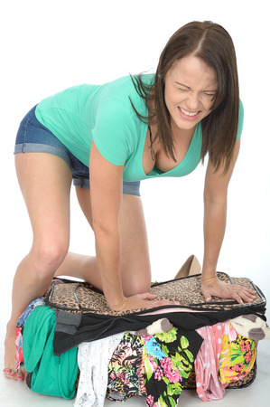 straining: Frustrated Attractive Young Woman Trying to Close and Over Filled Suitcase