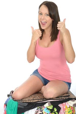 mujer arrodillada: Feliz joven mujer de rodillas y que intenta cerrar su maleta Overfull sonriente en un chaleco rosado Top