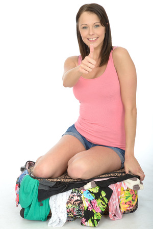 Happy Young Woman Kneeling and Trying to Close Her Overfull Suitcase Smiling in a Pink Vest Top photo