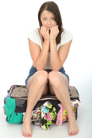 a situation alone: Nervous Scared Attractive Young Woman Sitting on a Suitcase Looking Worried