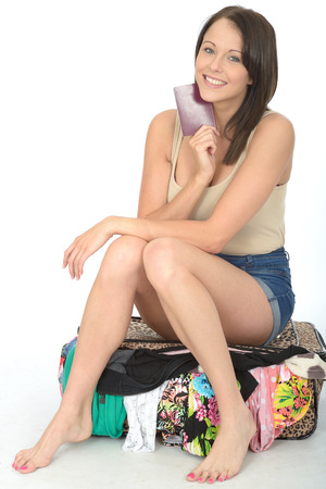 a situation alone: Happy Pleased Attractive Young Woman Holding a Passport Sitting on a Suitcase Smiling