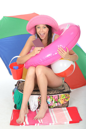 a situation alone: Happy Excited Young Woman Smiling and Laughing with a Rubber Ring Beach Ball and Bucket Sitting on a Suitcase Full of Clothes Smiling Stock Photo