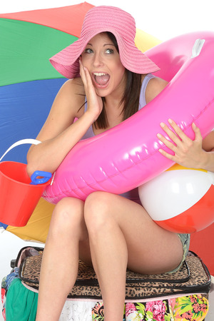 rubber ring: Happy Excited Young Woman Smiling and Laughing with a Rubber Ring Beach Ball and Bucket Sitting on a Suitcase Full of Clothes Smiling Stock Photo