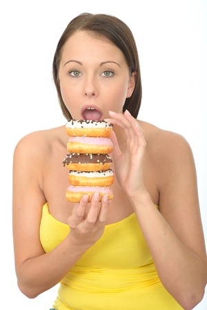 tempting: Attractive Young Woman in Her Twenties Holding a Pile of Tempting Iced donuts Stock Photo