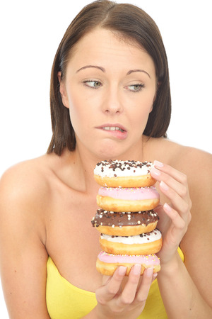 a situation alone: Attractive Young Woman in Her Twenties Holding a Pile of Tempting Iced donuts Stock Photo