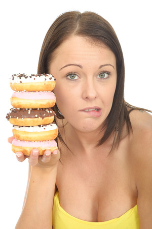 the twenties: Attractive Young Woman in Her Twenties Holding a Pile of Tempting Iced donuts Stock Photo