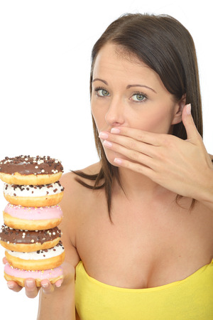 Attractive Young Woman in Her Twenties Holding a Pile of Tempting Iced donuts Stock Photo