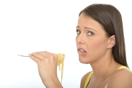 a situation alone: Portrait of a Young Woman in Her Twenties Eating A Fork Full of Cooked Spaghetti Pasta