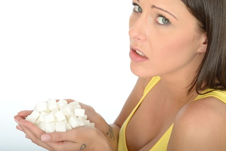 Attractive Young Woman in Her Twenties Holding a Handful of White Sugar Cubes Looking at the Camera
