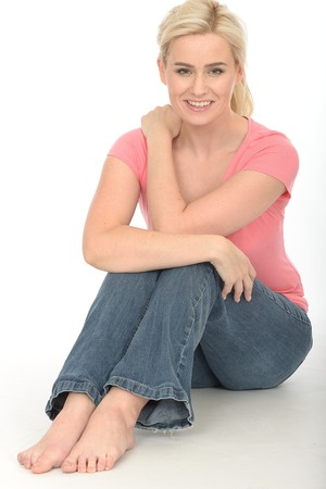 twenties: Happy Thoughtful Young Woman in Her Twenties Sitting on the Floor Relaxing and Attractive Stock Photo