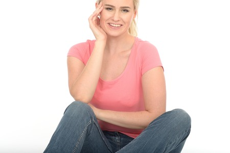 Happy Thoughtful Young Woman in Her Twenties Sitting on the Floor Relaxing and Attractive photo
