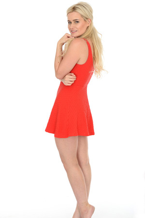 bare feet: Attractive Sexy Young Blonde Haired Woman in Her Twenties Wearing a Short Red Mini Dress in Bare Feet Stock Photo