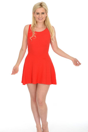 blonde haired: Attractive Sexy Young Blonde Haired Woman in Her Twenties Wearing a Short Red Mini Dress in Bare Feet Stock Photo
