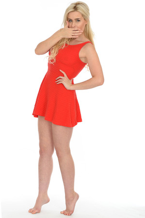 Attractive Sexy Young Blonde Haired Woman in Her Twenties Wearing a Short Red Mini Dress in Bare Feet Stock Photo