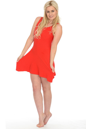 mini dress: Attractive Sexy Young Blonde Haired Woman in Her Twenties Wearing a Short Red Mini Dress in Bare Feet Stock Photo