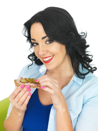 gherkin: Young Healthy Woman Eating a Cracker with German Sausage and Gherkin